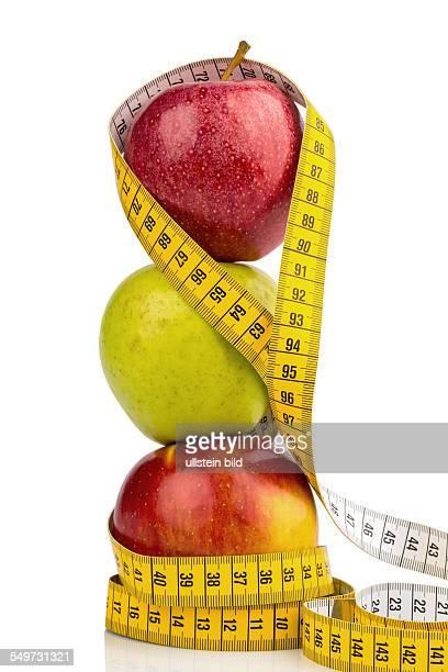 Mehrere Äpfel mit einem Maßband Symbolfoto für Diät und gesunde vitaminreiche Ernährung