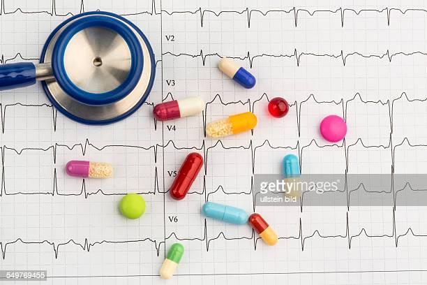Mehrere Tabletten liegen auf einem EKG Symbolfoto für Erkrankungen von Herz und Kreislauf