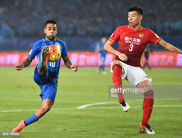 Mei Fang of Guangzhou Evergrande and Alex Teixeira of Jiangsu Suning vie for the ball during the final second leg of Yanjing Beer 2016 Chinese...
