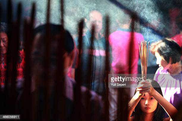 Mei Ling holds incense sticks as she attends prayers during Chinese New Year celebrations for the Year of The horse at Bahtara Sasana Temple on...