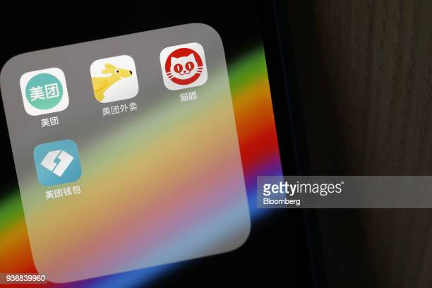 Meituan Dianping application icons Meituan clockwise from left Meituan Waimai Maoyan and Meituan Wallet are displayed on an Apple Inc iPhone in an...