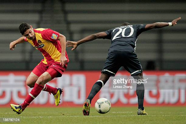 Mejdi Traoui of Esperance Sportive de Tunis is challenged by Walter Ayovi of Monterrey during the FIFA Club World Cup 5th Place match between Club de...