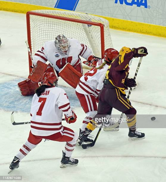 Mekenzie Steffen of the Wisconsin Badgers battles left wing Sarah Potomak of the Minnesota Golden Gophers as Badgers goalie Kristen Campbell and...