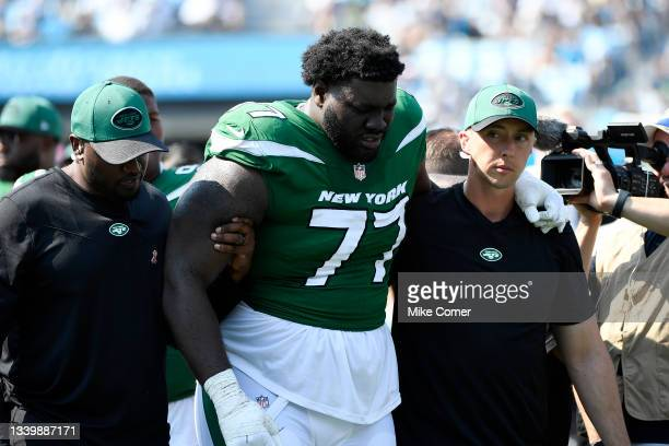 Mekhi Becton of the New York Jets is helped off the field after being injured during the third quarter against the Carolina Panthers at Bank of...