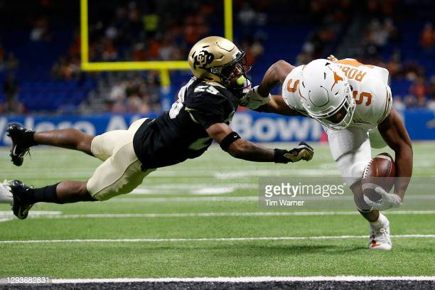 Mekhi Blackmon of the Colorado Buffaloes attempts to tackle Bijan Robinson of the Texas Longhorns as he rushes for a touchdown in the first quarter...