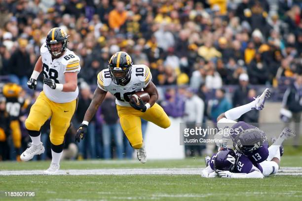 Mekhi Sargent of the Iowa Hawkeyes is tripped up by Bryce Jackson and JR Pace of the Northwestern Wildcats during the first quarter at Ryan Field on...