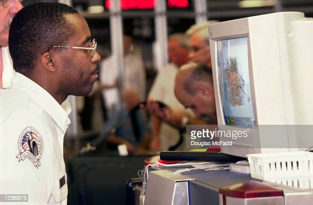 Mel Burl a Transportation Security Administration screener inspects bags with a xray machine August 6 2002 in Terminal C of Logan Airport in Boston...