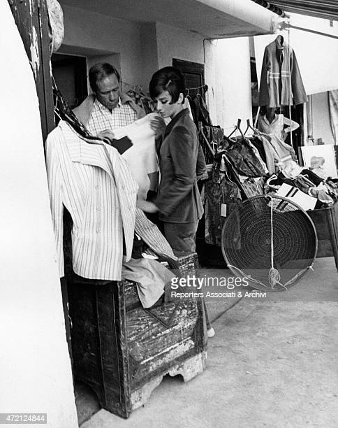 'Mel Ferrer trying on a dress together with his wife Audrey Hepburn between the outside benches of a clothing store the Oscar winner actress is here...