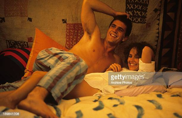 Mel Gibson and Joanne Samuel in bed laughing in a scene from the film 'Mad Max', 1979.