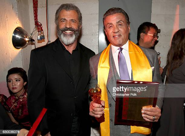 Mel Gibson and Sylvester Stallone pose backstage during the 21st Annual Huading Global Film Awards at The Theatre at Ace Hotel on December 15 2016 in...