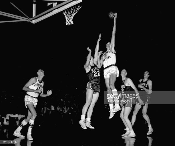Mel Hutchins of the Fort Wayne Zollner Pistons tries to score as Al Ferrari of the St Louis Hawks tries to block the shot during a Western Division...