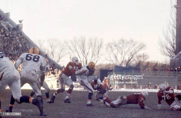 Mel Meyers of the Illinois Fighting Illini runs with the ball as Henry Derleth of the Wisconsin Badgers goes for the tackle during an NCAA game on...