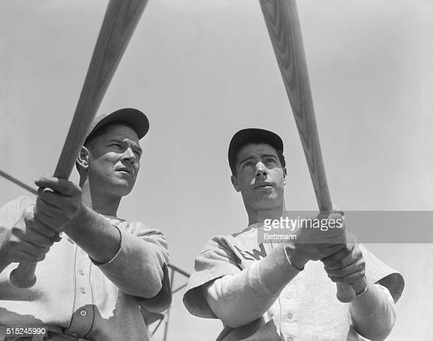 Mel Ott, diminutive slugger for the New York Giants, poses with home run hitter Joe DiMaggio of the Yankees with their weapons aloft before they took...
