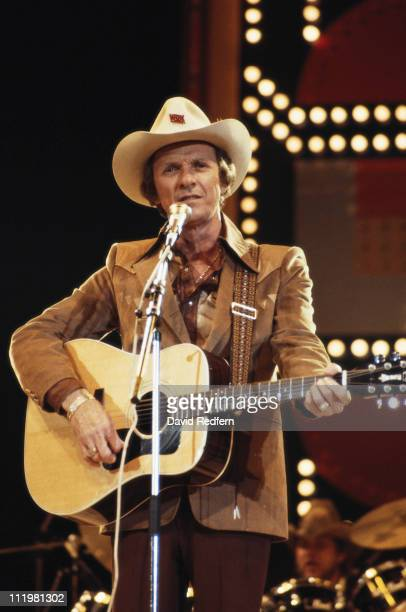 Mel Tillis US country singer singing into a microphone while playing the guitar during a concert circa 1982
