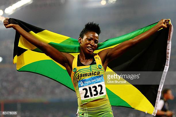 Melaine Walker of Jamaica celebrates with her countries flag after winning the Women's 400m Hurdles Final at the National Stadium during Day 12 of...