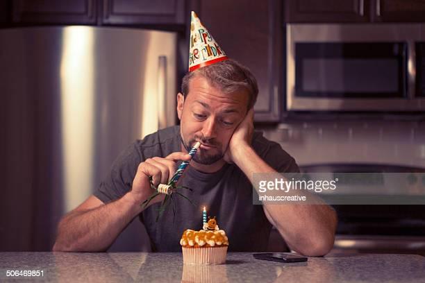 Melancholy man at home celebrating her birthday all alone