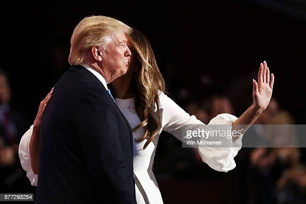 Melania Trump kisses her husband and presumptive Republican presidential nominee Donald Trump, after delivering a speech on the first day of the...