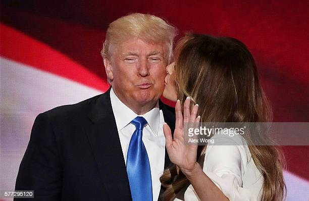 Melania Trump kisses her husband and presumptive Republican presidential nominee Donald Trump after delivering a speech on the first day of the...