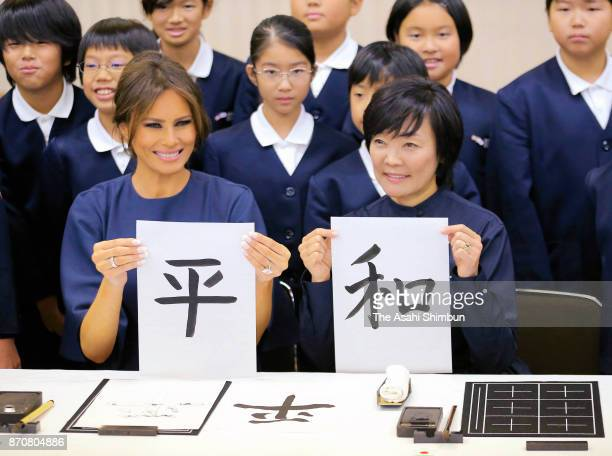 Melania Trump wife of US President Donald Trump and Akie Abe wife of Japanese Prime Minister Shinzo Abe show their calligraphy read 'Peace' during...
