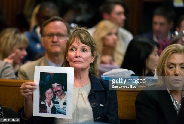 Melanie Barbeau holds a photograph of victims Cheri Domingo and Greg Sanchez during the arraignment of Joseph James DeAngelo the suspected East Area...