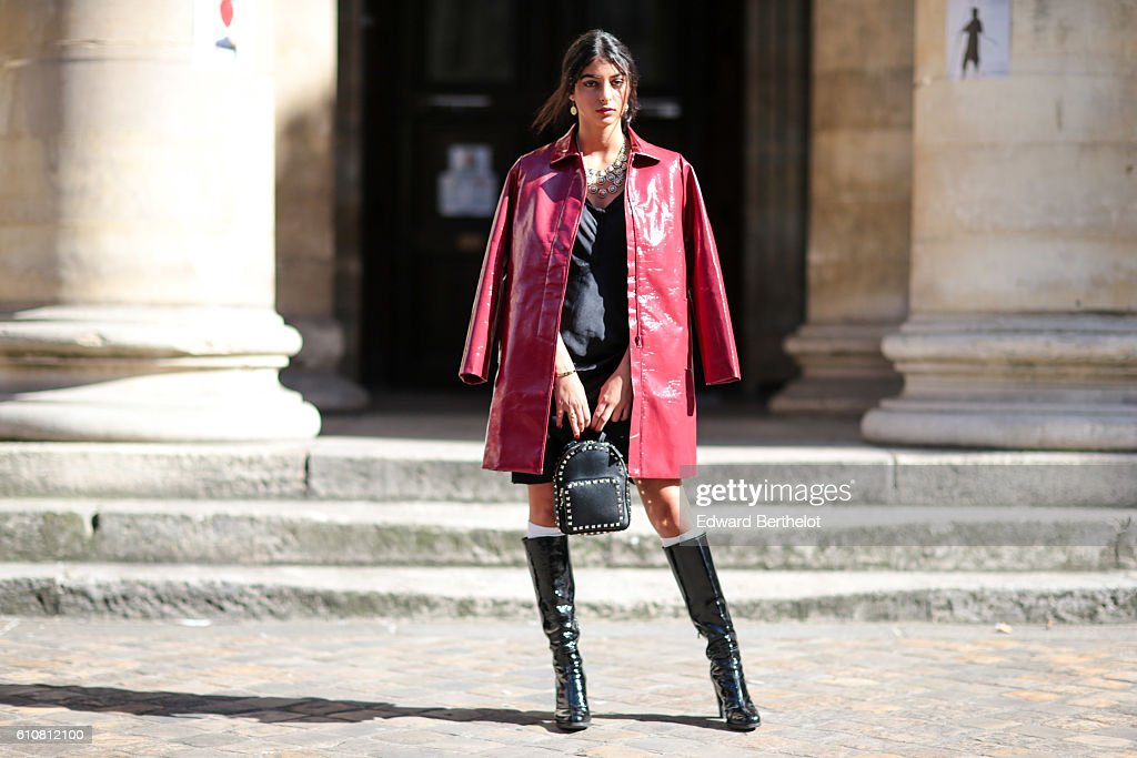 Melanie Darmon, fashion blogger, is wearing a red coat, black dress, black bag, and black boots outside the Nehera show on September 27, 2016 in Paris, France.