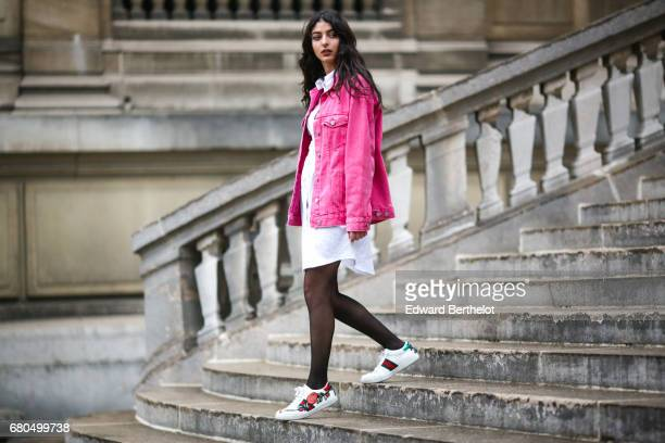 Melanie Darmon wears a Bershka pink denim jacket an HM white dress shirt Lise Paris jewelry and Gucci sneakers shoes on May 8 2017 in Paris France