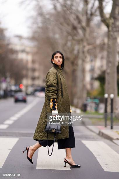 Melanie Darmon wears a green khaki long quilted padded puff winter coat from Aigle, a black yellow and white floral print shirt from Versace, black...