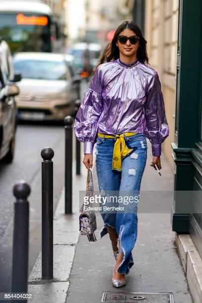 Melanie Darmon wears a purple shiny ruffled top a yellow belt blue denim jeans silver shoes outside Anrealage during Paris Fashion Week Womenswear...