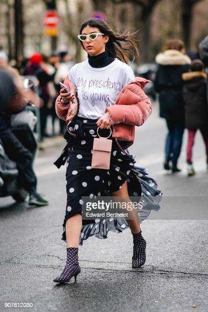 Melanie Darmon wears sunglasses a pink puffer coat a white tshirt a black lace mesh skirt with polka dots outside Dior during Paris Fashion Week...