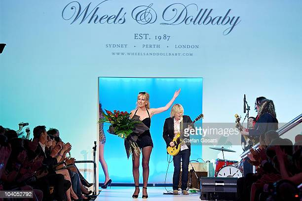 Melanie Greensmith acknowledges the crowd while Mark McEntee performs on the catwalk during the Wheels & Dollbaby collection catwalk show as part of...