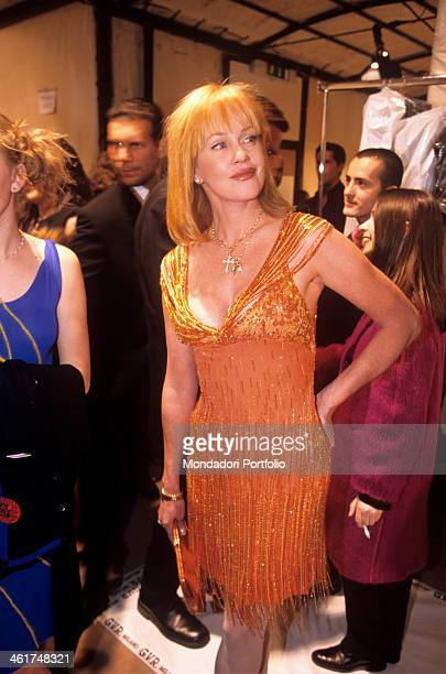Melanie Griffith in a sequined orange dress with fringes smiles in the backstage of the Versace fashion show standing beside Bridget Michael Sumner...