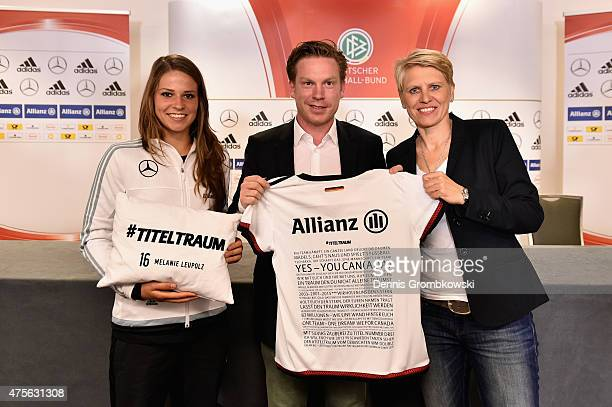 Melanie Leupolz and team manager Doris Fitschen of Germany pose with Peter Kort head of sponsorship Allianz AG presenting a shirt and a pillow...