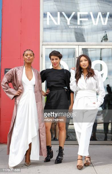 Melanie Liburd is seen wearing a white maxi dress, a mauve trench coat, and metallic pumps and Jeannie Mai is seen wearing white jumpsuit with a...