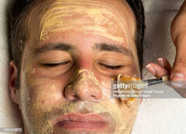 Melanie Mari owner of BareSkin Studio in Laguna Hills applies a multivitamin power recovery mask to the face of Brea real estate agent Jonathan...
