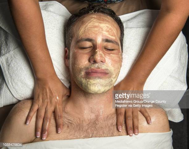 Melanie Mari owner of BareSkin Studio in Laguna Hills gives Jonathan McCarty a shoulder massage while a multivitamin power recovery mask is on his...