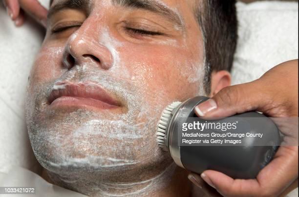 Melanie Mari owner of BareSkin Studio in Laguna Hills uses a Clarisonic exfoliating mens scrub brush to scrub the face of Brea real estate agent...