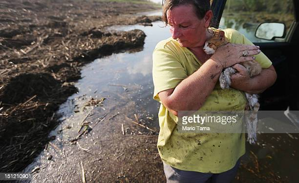 Melanie Martinez holds the family cat which they have renamed Isaac after salvaging items from their flooded home in Plaquemines Parish on September...