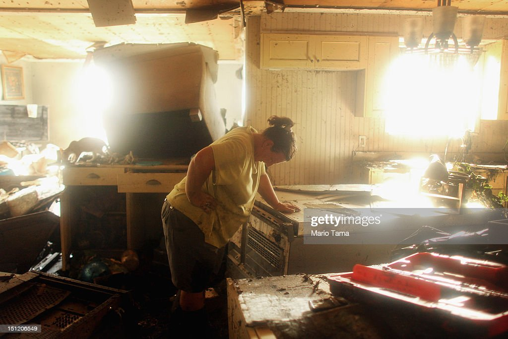 Melanie Martinez pauses while salvaging items in her flooded home in Plaquemines Parish on September 3, 2012 in Braithwaite, Louisiana. Martinez, along with her husband and mother, was forced to ride out the storm in the home when their car broke down. The house quickly flooded and they were rescued by a neighbor who was able to break into their attic to save them. This is the fifth home Martinez has had destroyed due to hurricanes in Louisiana. Damage totals from the hurricane could top $2 billion and more than 125,000 customers are still without power six days after the storm made landfall.