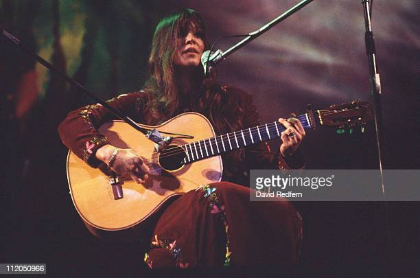Melanie US singersongwriter performing live in concert playing the guitar while singing into a microphone circa 1970