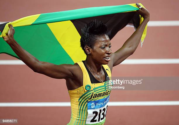 Melanie Walker of Jamaica hoists her national flag as she celebrates winning the gold medal in the women's 400meter hurdles on day 12 of the 2008...