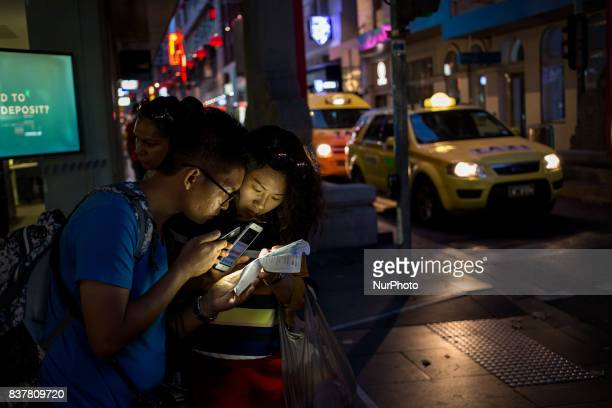 Melbourne Australia 16 march 2017 Two tourists check their map at night near the chinese district Melbourne is ranked as the worlds most liveable...