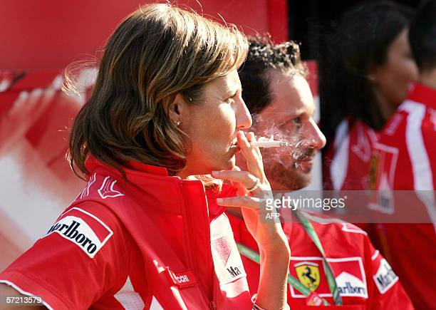 A Ferrari crew member emblazoned in Marlboro emblems enjoys a cigarette as the Formula One teams arrive at Albert Park in Melbourne 30 March 2006 The...