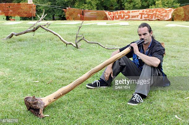 A man plays a traditional didgeridoo instrument near a park where an ongoing Aborigine demonstration against the visit of Queen Elizabeth II and the...
