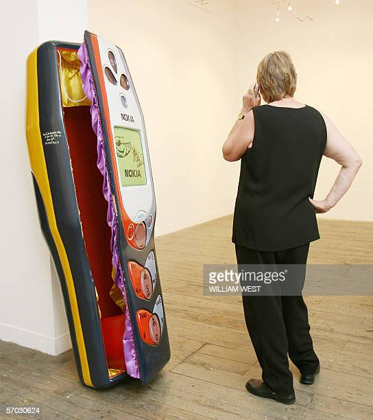 A woman speaks on a phone next to a coffin carved in the shape of a mobile phone by the Paa Joe Carpentry workshop in Ghana and commissioned for...