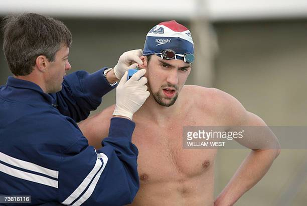An official takes a blood sample from the ear of US swimming superstar Michael Phelps during a practice session 17 March 2007 in Melbourne a few days...