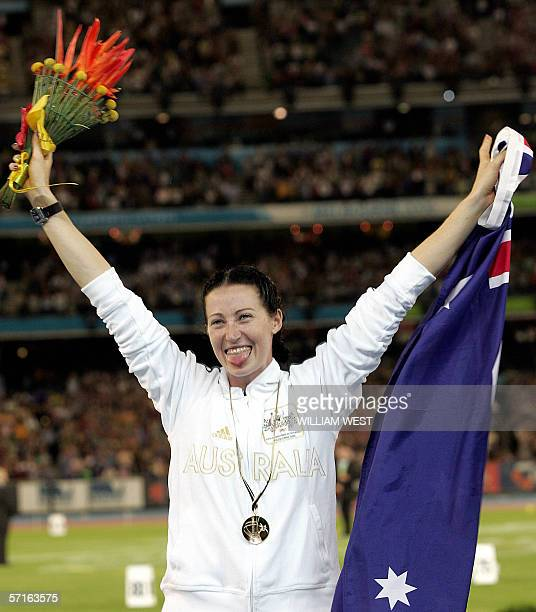 Autralian Jana Pittman celebrates on the podium during the medals ceremony after winning the women's 400m hurdles final at the Commonwealth Games in...
