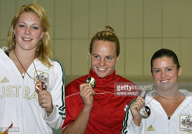 Canada's Blythe Hartley with Australian's Chantelle Newbery and Kathryn Blackshaw alongside shows her gold medal after winning the Commonwealth Games...