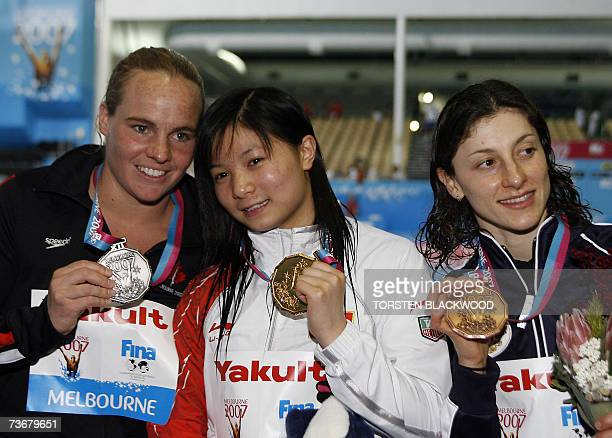 China's He Zi displays her gold medal with Canadian silver medalist Blythe Hartley and Russian bronze medalist Yuliya Pakhalina after the women's 1m...