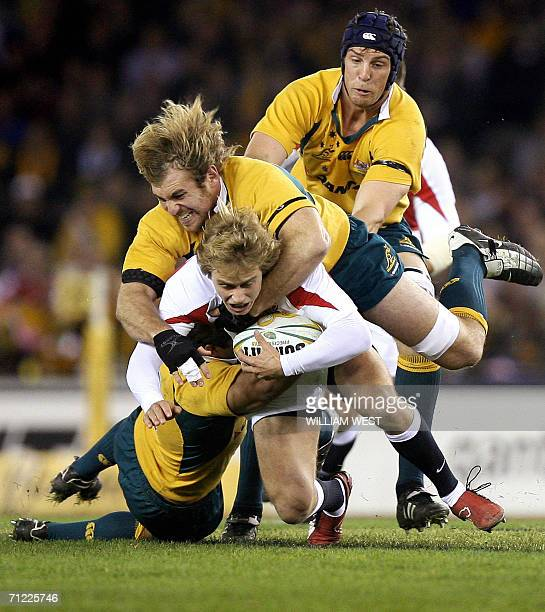 England winger Matthew Tait is driven into the ground by Australia defenders Rocky Elsom and Daniel Vickerman during the second Test Match being...