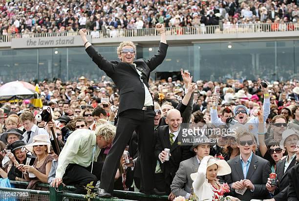 Fans celebrate in the huge crowd as Japanese horse Delta Blues wins the five million Australan dollar Melbourne Cup horse race 07 November 2006 Delta...